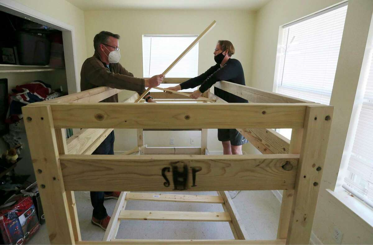 Shane Arnold (left) and his son Gavin, 15, install a bunk bed from Sleep in Heavenly Peace at Jessica Cabot's home on Christmas Eve. Since 2018, the nonprofit Sleep in Heavenly Peace has built and delivered beds to families who were in need of beds for children who mostly slept on air mattresses, couches or even on floors.