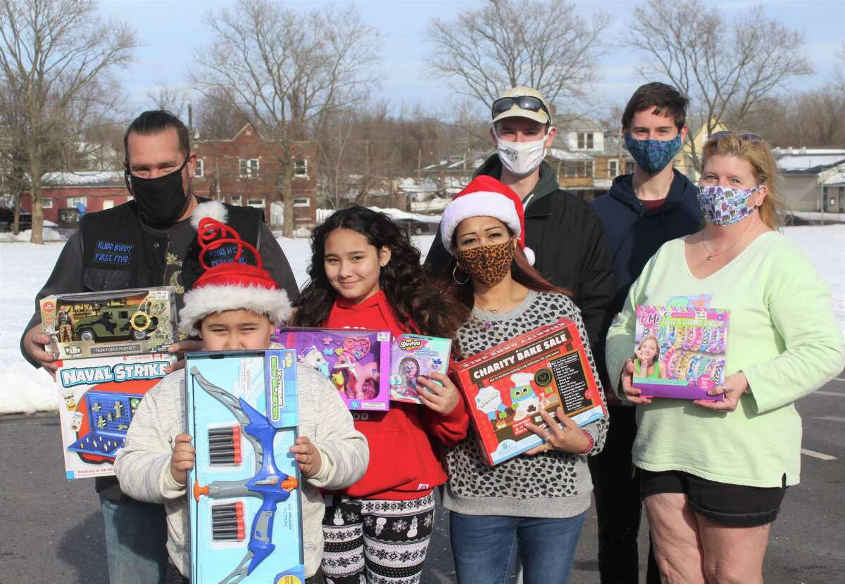 From left, The Knights of Valhalla club president Bill Perkins, his children Collin and Mia Perkins, Perkins' wife Carel Perez Perkins, Kyle and Kurt Kapacziewski, and their mother Tami Kapacziewski, pose for a photo at Macdonough Elementary School in Middletown. All were among volunteers who distributed toys to families who live in the North End.