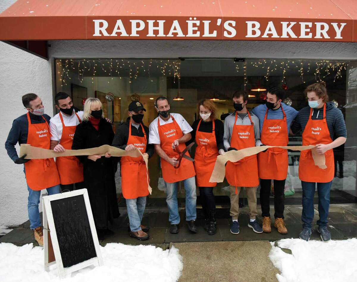 Owner Raphaël Dequeker cuts the ribbon beside his wife and business co-owner Charlotte Dequeker and First Selectman Fered Camillo, to his left, at the opening of Raphaël's Bakery in Greenwich, Conn. Sunday, Dec. 20, 2020. Located at 146 Mason St., the French Bakery features fine bread, patisserie, and espresso from the former head pastry chef at Valbella in Riverside.