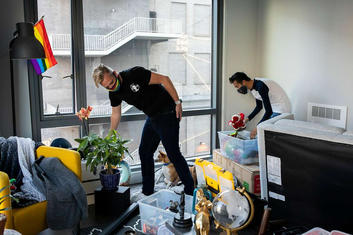 Christopher Beale (left) and Reagan Rockzsfforde unpack in their new S.F. apartment after moving from Oakland last month.