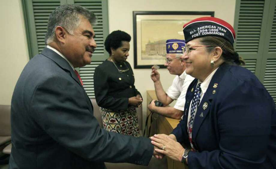 Joe A. Pina, a veterans court defense lawyer, greets Sylvia C. Sanchez of VFW Westside Post 8936 as Grace M. Uzomba, also a defense lawyer, chats with Bill Johnson, adjutant of Alamo Chapter 1836 Military Order of the Purple Hearst, after the news conference.