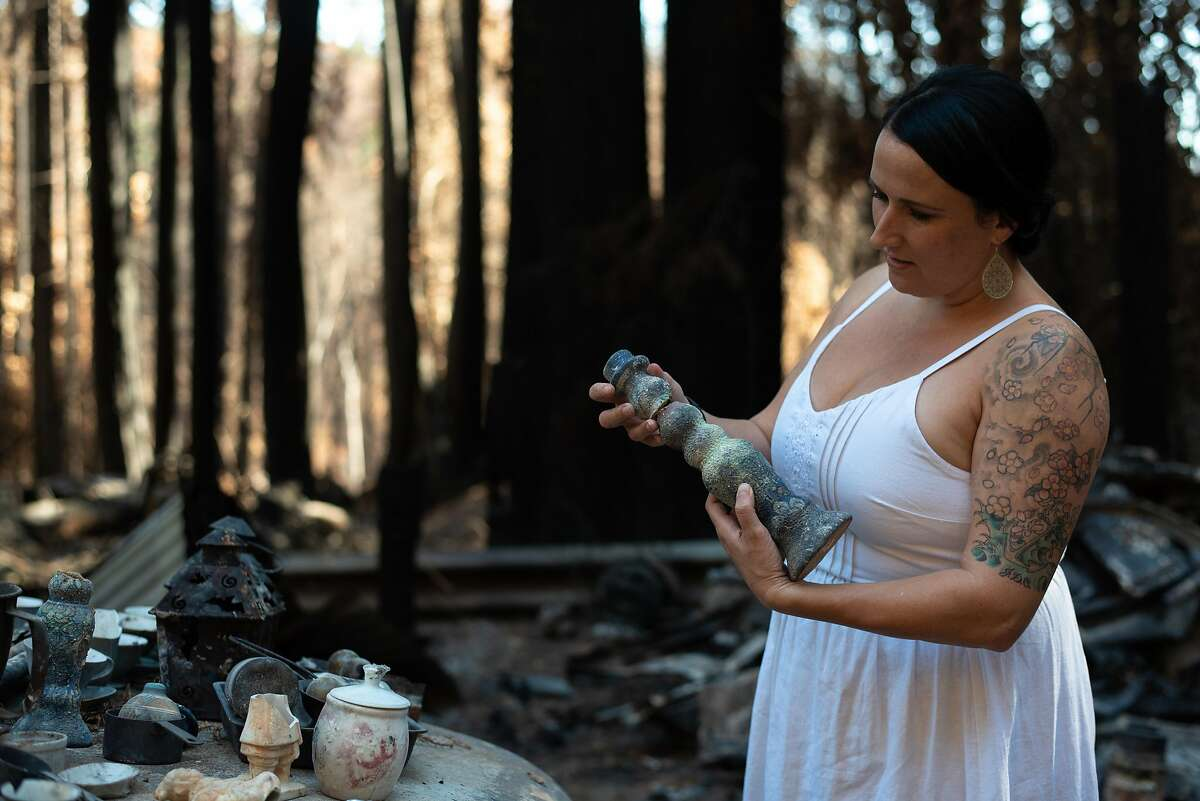 Antonia Bradford shows some of the possessions recovered at the site of her home in Boulder Creek (Santa Cruz County), which was destroyed by the CZU Lightning Complex in September.
