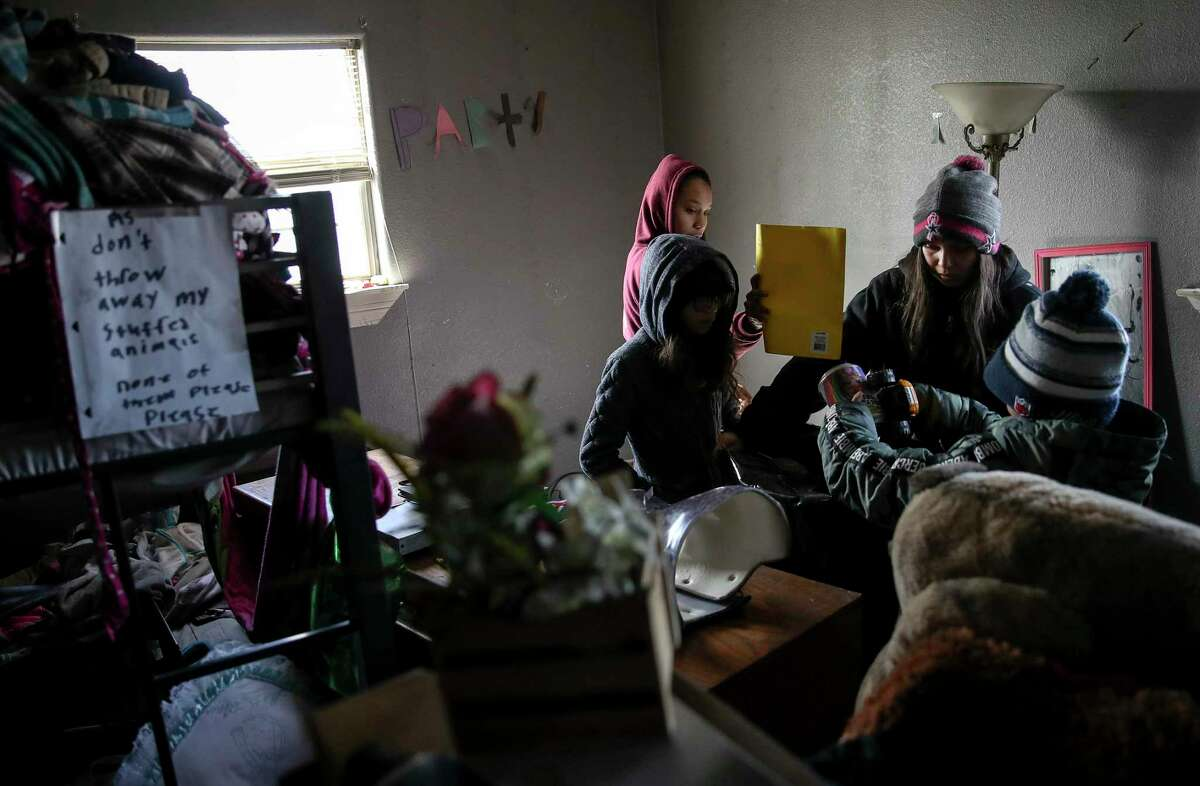 """Aileen Manriquez, 14, clockwise from rear left, her mother Alicia, her brother Andrew, 9, and sister Amy, 10, sort items to be cleaned or thrown away Thursday, Dec. 24, 2020, at their home in New Caney, Texas. A fire destroyed much of their home and belongings Dec. 15, the family said. """"We didn't just lose our stuff, we lost our home that we thought we were safe in,"""" the mother said. After the fire, East Montgomery County firefighters and Splendora police officers brought toys and bikes to the family, the mother said as she choked up. """"It was overwhelming, I don't have words,"""" she said. """"The one thing I think we need most is clothing, shoes and food,"""" she said."""