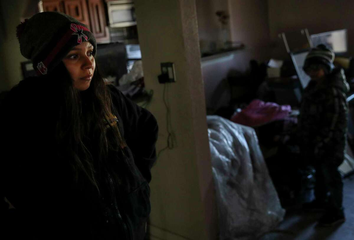 """Alicia Manriquez becomes emotional as she looks at a space where her Christmas tree once stood Thursday, Dec. 24, 2020, at her home in New Caney, Texas. A fire destroyed much of the home and belongings Dec. 15, the family said. """"We didn't just lose our stuff, we lost our home that we thought we were safe in,"""" she said. After the fire, East Montgomery County firefighters and Splendora police officers brought toys and bikes to the family, the mother said as she choked up. """"It was overwhelming, I don't have words,"""" she said."""
