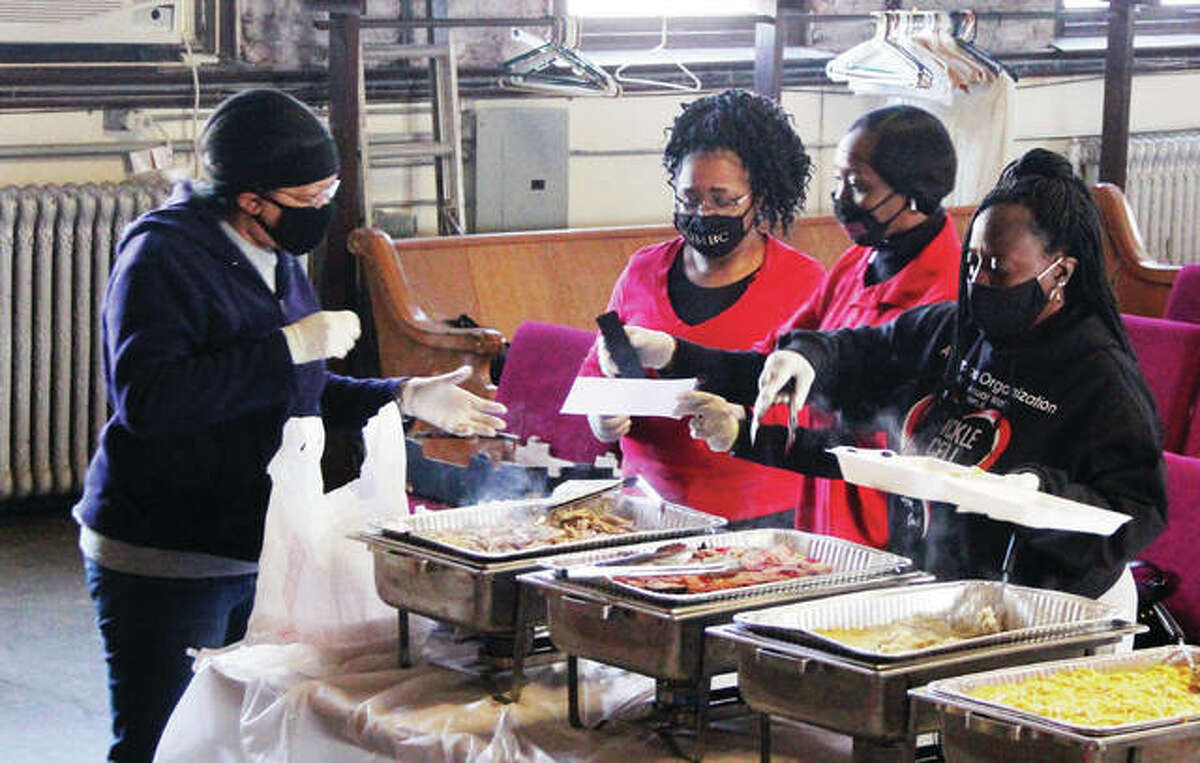 """Members of St. John Missionary Baptist Church in Alton prepare food for community members Friday morning as part of the church's annual Christmas Dinner Friday morning. More than 100 individuals or families signed up for a free Christmas dinner, with additional """"walk-ins"""" expected. Because of COVID the church switched to a """"drive-in"""" format this year, and was also hampered because the church's furnace was out."""