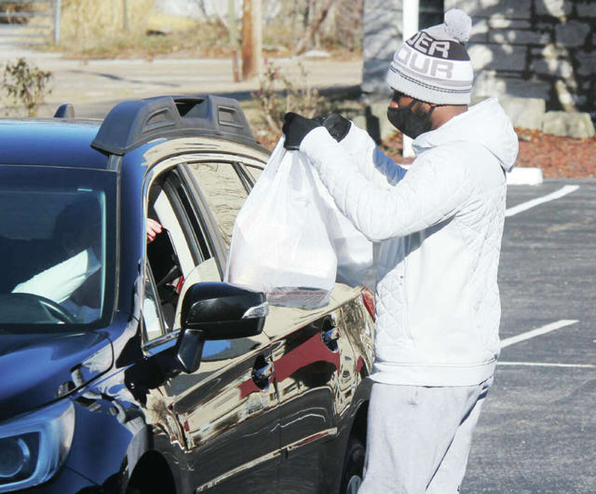 """A volunteer from St. John Missionary Baptist Church in Alton takes food out to waiting community members as part of the church's annual Christmas Dinner Friday morning. More than 100 individuals or families signed up for a free Christmas dinner, with additional """"walk-ins"""" expected. Because of COVID the church switched to a """"drive-in"""" format this year, and was also hampered because the church's furnace was out."""