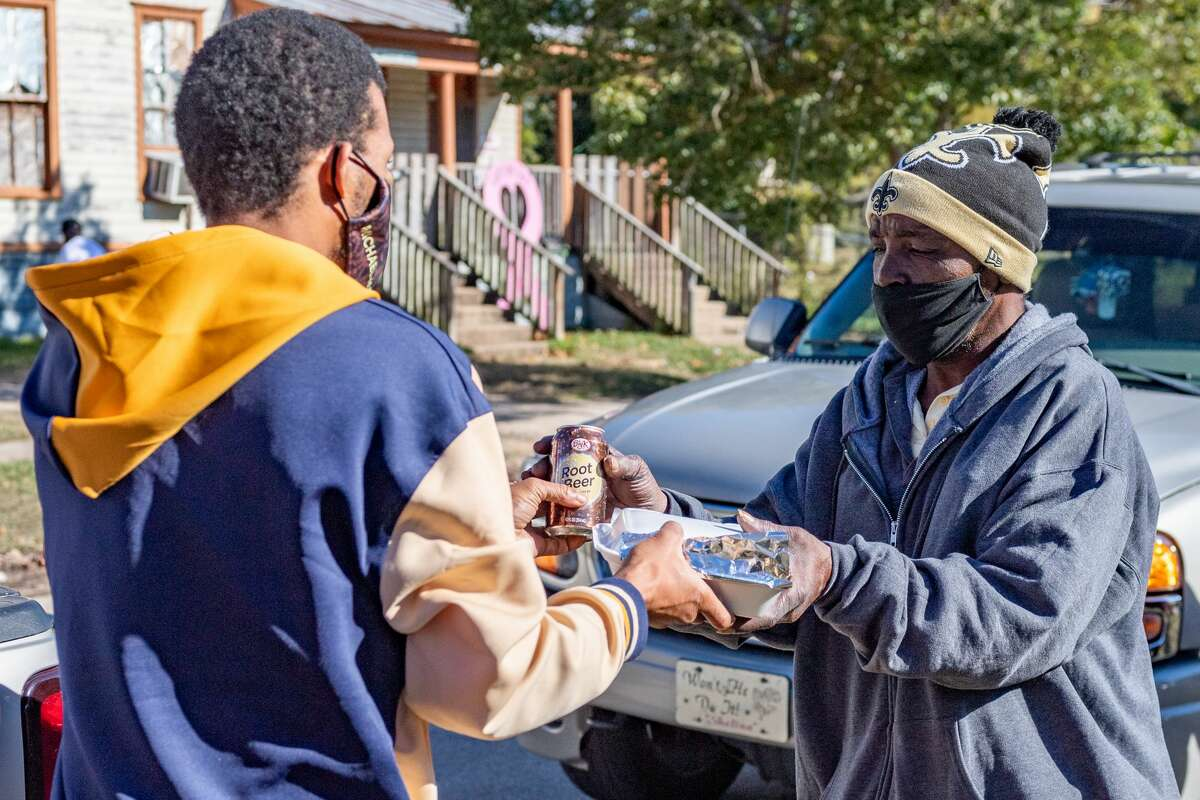 A member of the group from the Orange Church of God Embassy of Grace gives a meal to one of the homeless men outside Some Other Place on McFaddin Street in Beaumont. Some Other Place and members of the church were out all morning on Christmas providing to-go meals to people experiencing homelessness and others in need. Photo made on December 25, 2020. Fran Ruchalski/The Enterprise