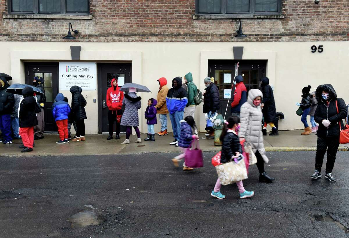 Families wait in line for a Christmas present distribution at the Capital City Rescue Mission on Friday, Dec. 25, 2020, in Albany, N.Y. Hundreds of bags filled with presents for people who need help obtaining or giving gifts were offered by volunteers. (Will Waldron/Times Union)