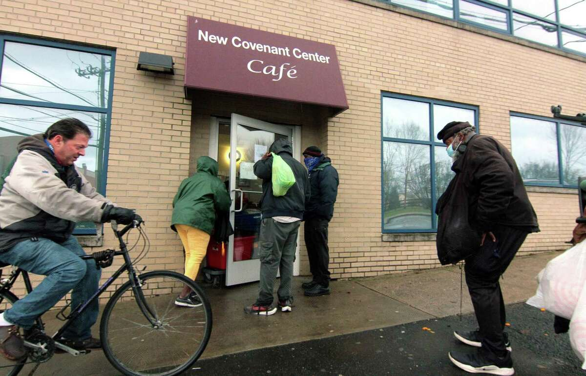 Guests pick up a take-out Christmas dinner in front of New Covenant Center in Stamford, Conn., on Friday Dec. 25, 2020. Volunteers from Temple Sinai helped prepare the dinners. The dinner is usually a sit-down service but the pandemic caused the annual event to be take-out only.