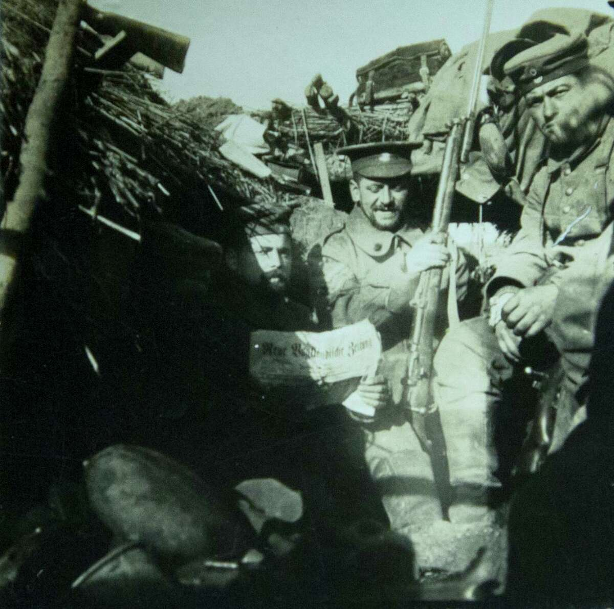 In this photo taken from an image in the collection at In Flanders Fields Museum provided by the family of German soldier Kurt Zehmisch, a German World War I soldier of the 103rd Saxon Regiment wears the hat of a British soldier as he sits in a trench with other German soldiers in Warneton, Belgium, during Dec. 1914.