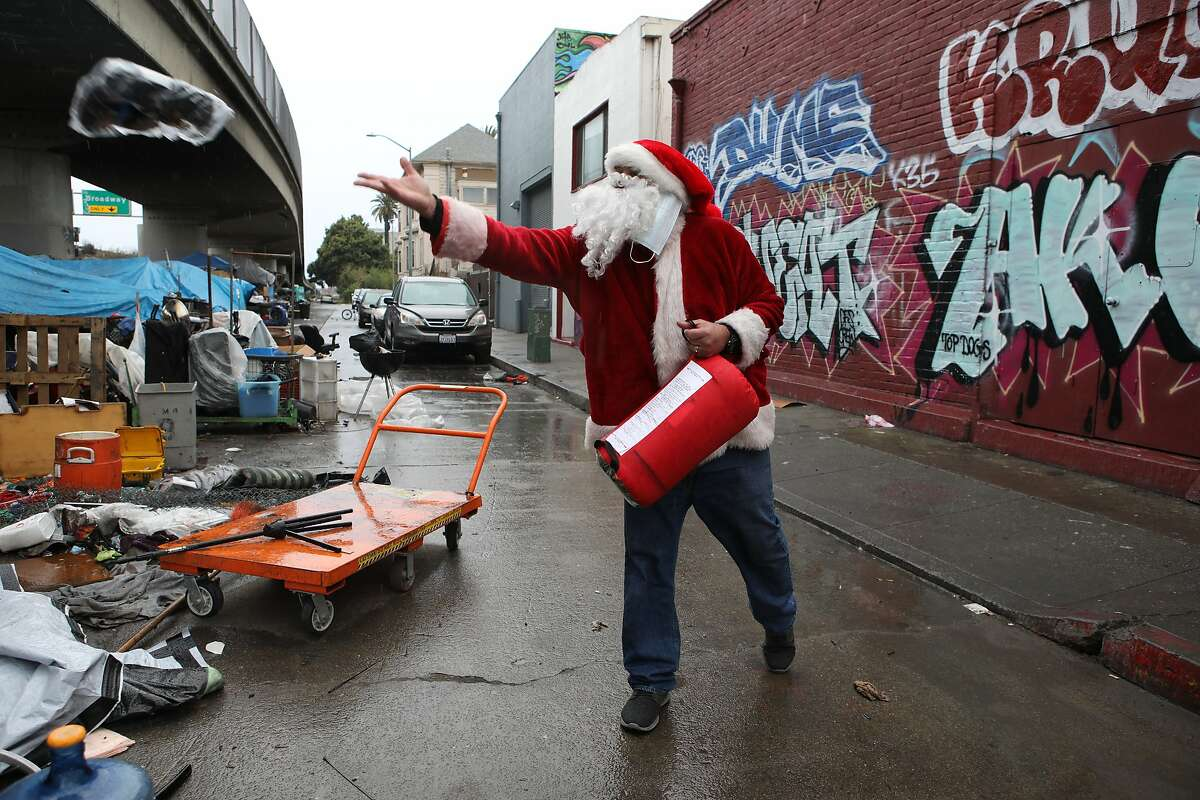 Roger Barcelona tosses socks to a homeless person in Oakland while carrying a sleeping bag for distribution.