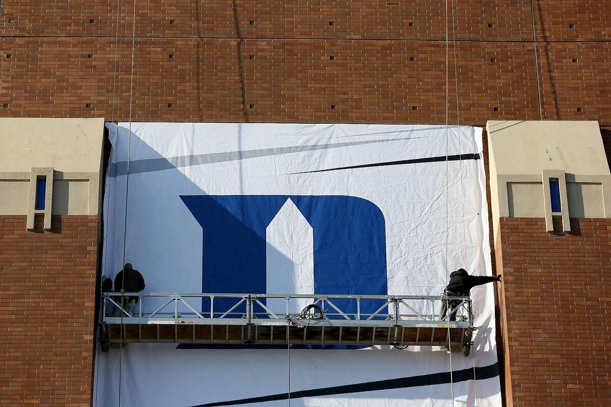 Workers hang the Duke Blue Devils logo on the side of Lucas Oil Stadium home of the 2015 Final Four on Indianapolis, Indiana in 2015. Duke women's basketball is opting out for the remainder of the season. (Streeter Lecka/Getty Images/TNS)