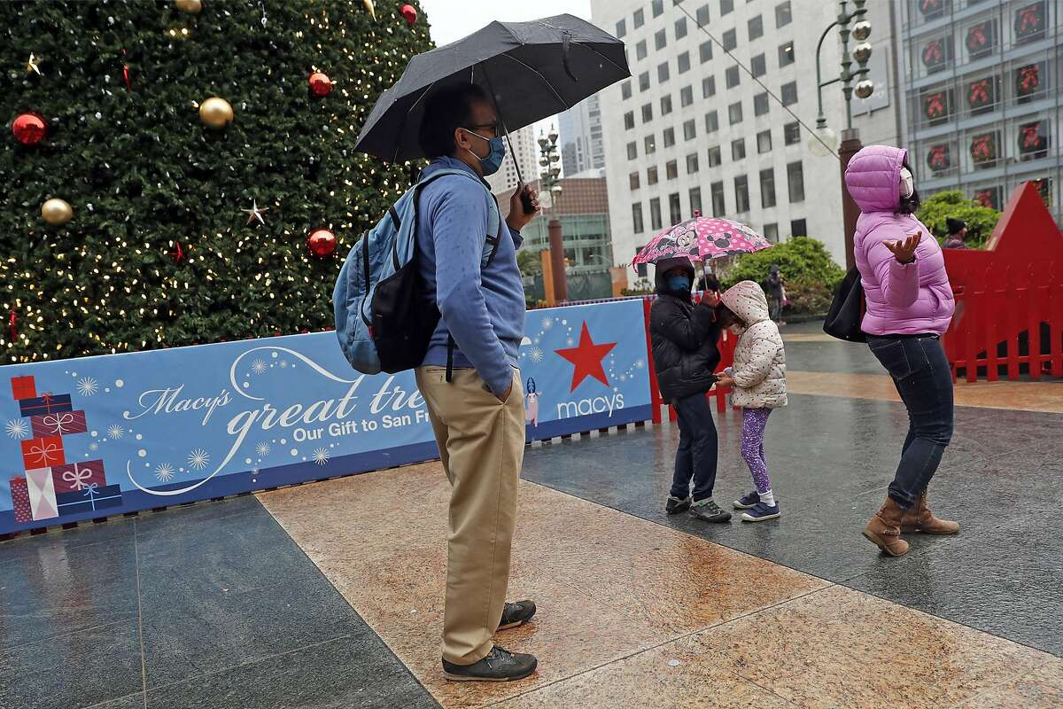 Reena Arya checks the rain, as her husband, Ambar, and children Sameer, 7, and Nuria, 4, stand under umbrellas at the Holiday tree in Union Square in San Francisco, Calif., on Friday, December 25, 2020.