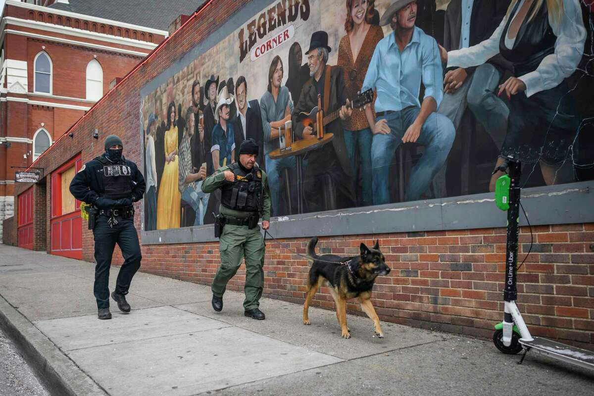 Police and a bomb-sniffing dog investigate an explosion Friday, Dec. 25, 2020.