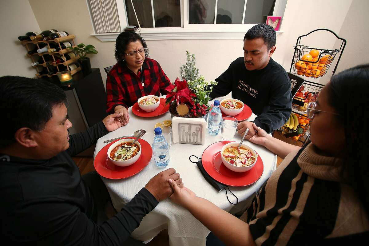 (Left-Right) Roberto Alvarez, (dad), Laura Alvarez, (mom), Roberto Alvarez, (son Tito), and Laura Alvarez, (daughter) hold hands during dinner prayer on Christmas Eve at the Alvarez family home in Redwood City, California on Thursday, December 24, 2019. Three out of the four family members recently recovered from Covid-19. Dad Roberto Alvarez remained negative for Covid-19 during his family's illness.