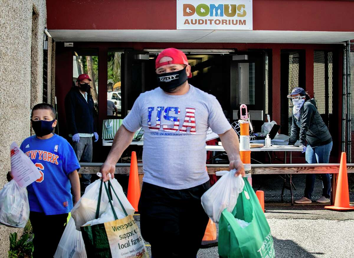 A man and boy leave the Domus Person to Person food pantry on Lockwood Avenue, Stamford. Person to Person works with beneficiaries of the Giving Fund.