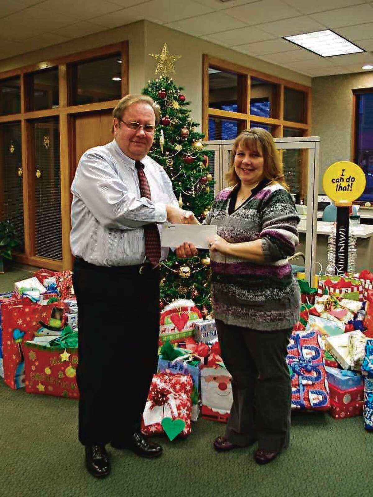 Steve Brower, Northwestern Bank's Manistee area vice president, presents a $500 check from the bank to Robin Paulus, executive director of Love INC of Manistee (now ECHO His Love) in December 2012.