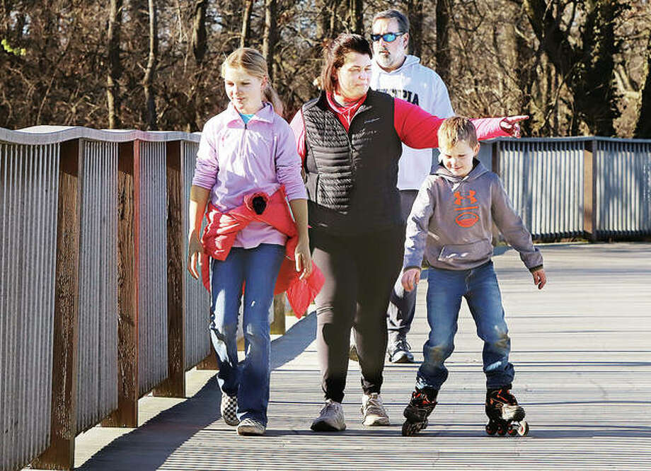 A group of people cross the walking bridge on the first day of Winter in Glazebrook Park Monday. Winter officially began Monday before dawn and is the shortest day of the year.