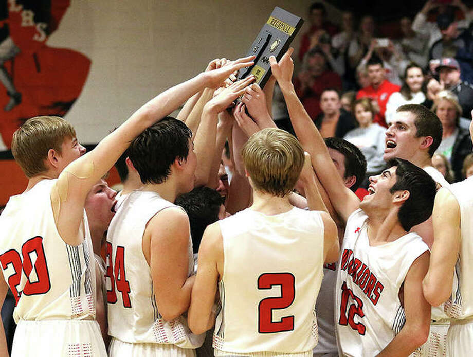 The Calhoun Warriors celebrate with the Class 1A regional championship plaque after beating host Raymond Lincolnwood last Feb. 27 in Raymond. The Warriors return four starters from that 25-8 squad. Photo: Greg Shashack / The Telegraph