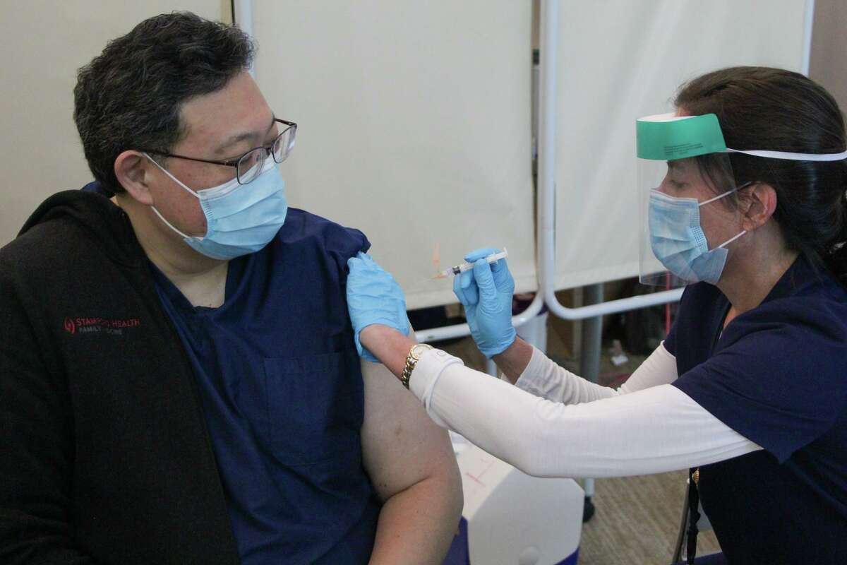 The city of Stamford's medical advisor, Dr. Henry Yoon, is vaccinated against the coronavirus at police headquarters on Thursday, Dec. 24, 2020.