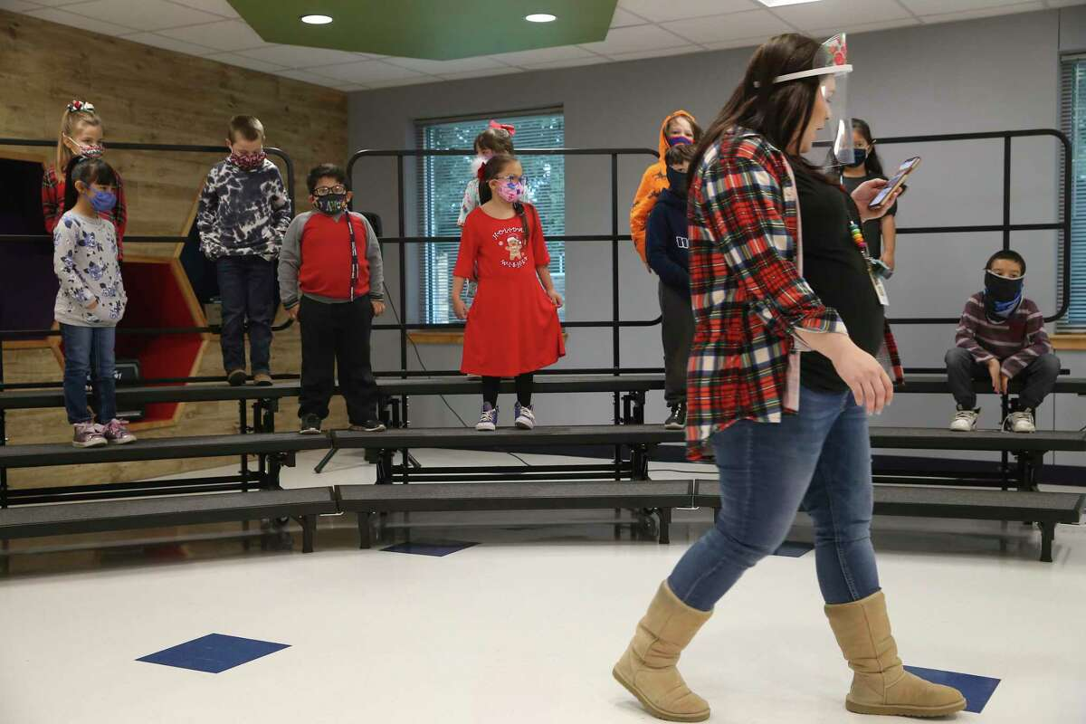 Art and music teacher Taylor Zipp arranges a class of first graders before rehearsing holiday songs at Meyer Elementary School in Hondo on the last day of the fall semester, Dec. 18, 2020. Hondo ISD stopped all remote learning on Nov. 9 with only medical exceptions allowed.