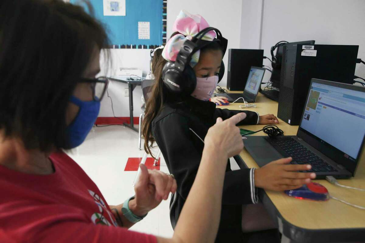 Teacher Carol Nichols helps first-grader Yamileth Conchas with her computer lesson at Meyer Elementary School in Hondo on the last day of the fall semester. Hondo ISD stopped all remote learning on Nov. 9 with only medical exceptions allowed.