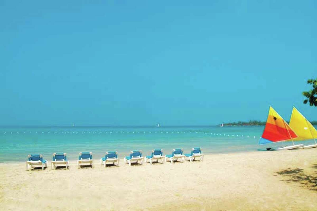 Beach chairs line the sandy shores of Jamaica.