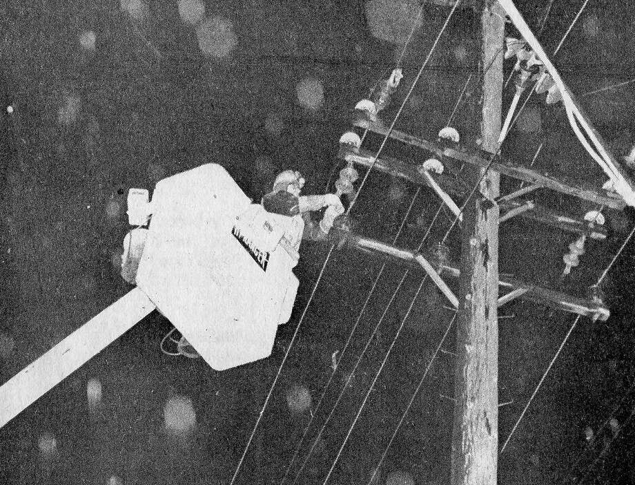 From the front page of the Manistee News Advocate on this day in 1980, a Consumer's Power Company employee works on an electric line during an ice storm that caused a blackout last night. (Manistee County Historical Museum photo)