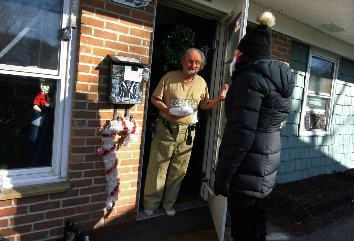 New American Dream Foundation Vice President Emanuela Palmares delivers a meal to senior citizen Patrick Flinch at Glen Apartments in Danbury, Conn., on Saturday Dec. 26, 2020. Volunteers spread out through Danbury to deliver well over 100 meals to residents at several other senior living facilities. Community donations, a $10,000 grant from the Tufts Health Plan Foundation and a $10,000 grant from the CT Health Foundation helped pay for the meals, made at cost by the Amber Room Colonnade. The organization has been delivering food to those in need throughout the pandemic. The Amber Room Colonnade made the meals at cost. Volunteers gathered at the Patriot Garage to set up and then distributed at eight housing communities.