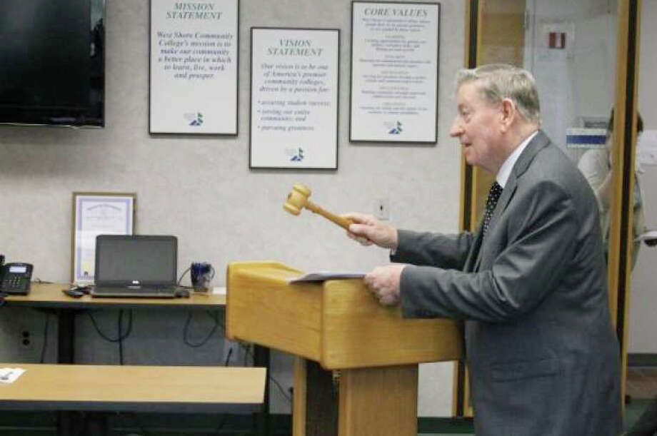 John Eaton who was the first president of West Shore Community College back calls a board of trustees meeting in March 2017 to order by banging the original gavel that was used at the first board of trustees meeting on March 27,1967. When Eaton retired years later, the gavel was presented to him by the board of trustees. Photo: File Photo