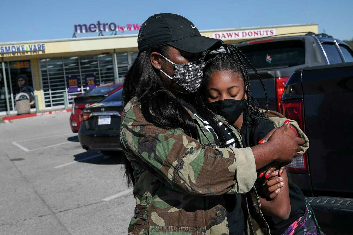 """Nisheka Jackson hugs her daughter Riley McKinney, 10, before a protest march Saturday, Dec. 26, 2020, in Texas City. About 150 people gathered to protest the killing of Joshua Feast, who was shot and killed by a La Marque police officer Dec. 9. """"I feel that everybody could be a target, so that's something she needs to be aware of,"""" Jackson said."""