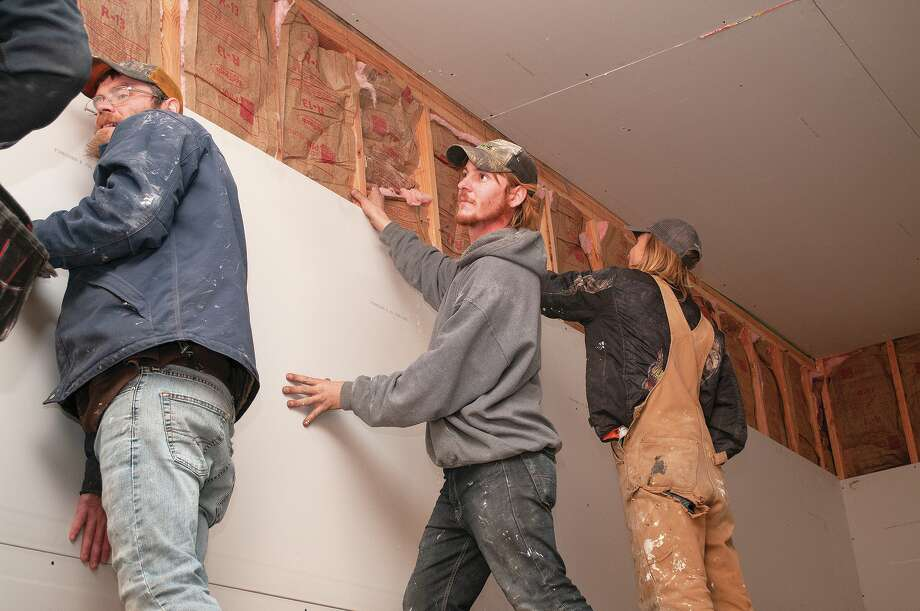 Walter Ellenburg (from left), Jesse Wismer and Blake Gum of C.L. Campbell Construction install drywall at 220 E. State St. The downstairs section is slated to be a candy cane-themed bar with four one-bedroom apartments upstairs. Photo: Darren Iozia, Darren Iozia | Journal-Courier / Jacksonville Journal-Courier