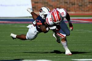 Louisiana running back Elijah Mitchell (15) runs through a tackle attempt by UTSA safety Rashad Wisdom in the first quarter during the SERVPRO First Responders Bowl NCAA college football game in Dallas, Saturday, Dec. 26, 2020. (AP Photo/Matt Strasen)