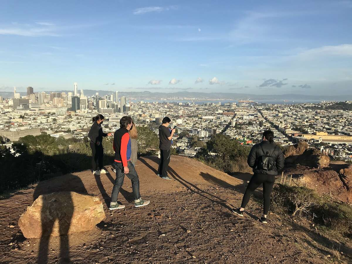 People stare at the area where the gingerbread monolith once stood in Corona Heights Park in San Francisco. Only some icing and crumbs, as well as a small shrine, remained at the site on Saturday.