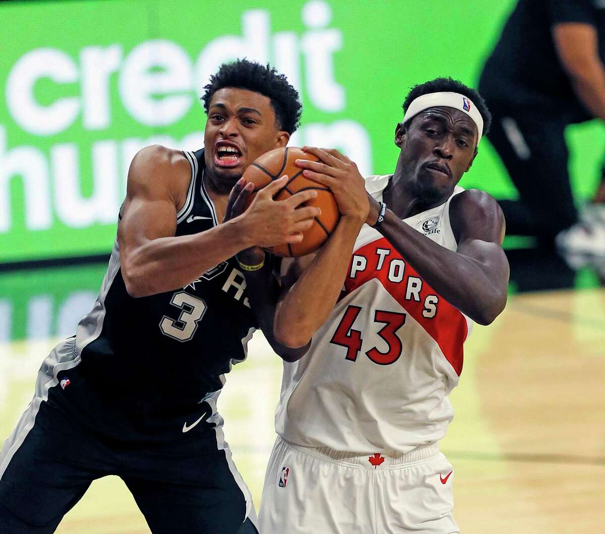 San Antonio Spurs guard Keldon Johnson (3) battles Pascal Siakam #43 of the Toronto Raptors for a rebound. Spurs v Raptors at AT&T Center on Saturday, Dec. 26, 2020.