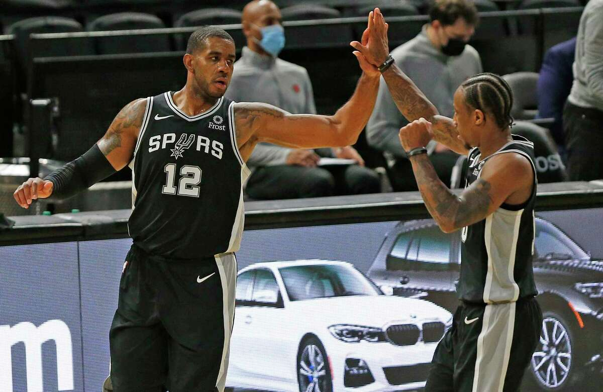 Spurs center LaMarcus Aldridge (12) receives a high-five teammate DeMar DeRozan (10) after his basket put the team ahead for good against the Toronto Raptors at the AT&T Center on Saturday, Dec. 26, 2020.