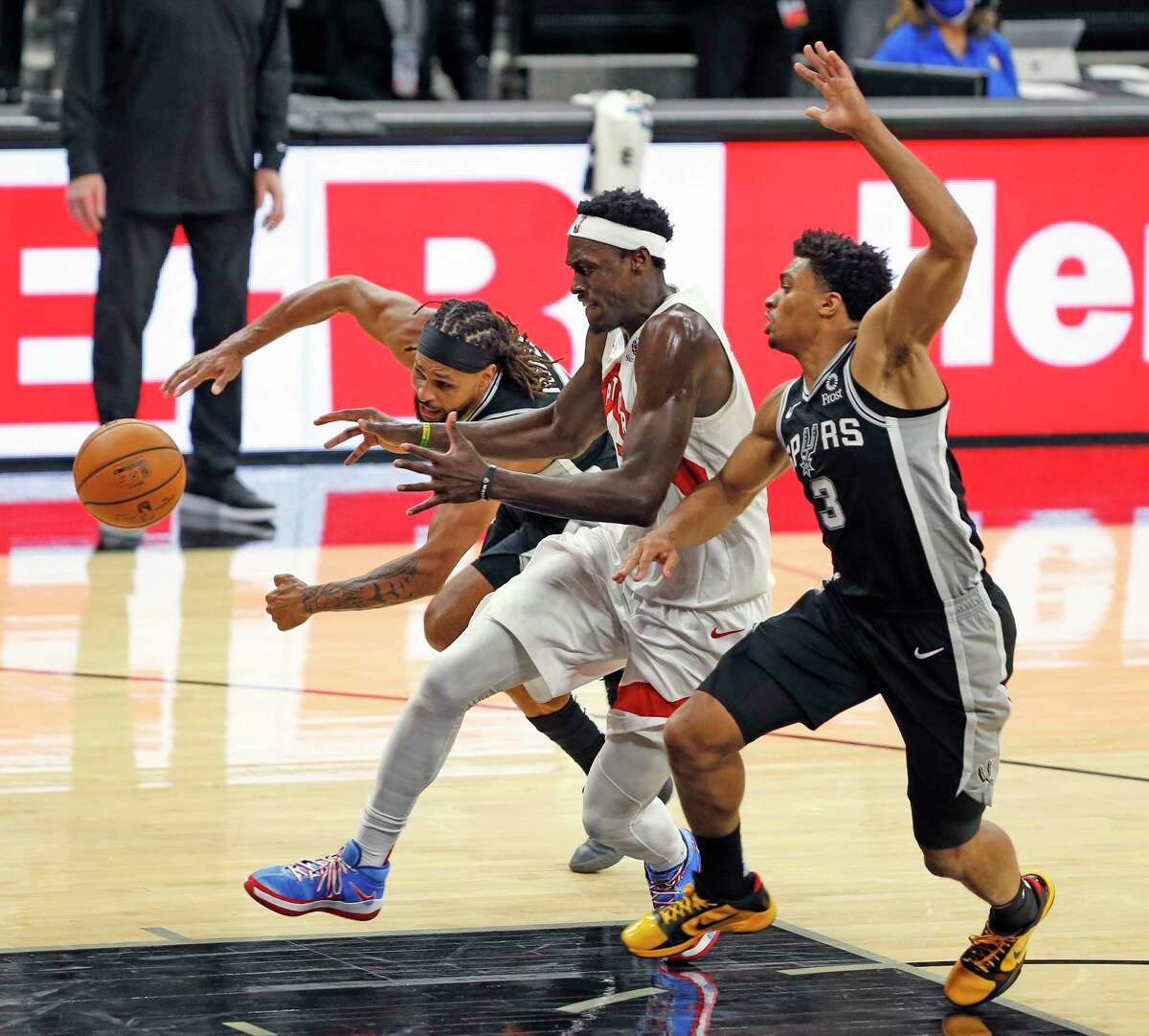 San Antonio Spurs guard Patty Mills (8) and guard Keldon Johnson (3) prevent Pascal Siakam #43 of the Toronto Raptors from scoring in closing minute of play. Spurs v Raptors at AT&T Center on Saturday, Dec. 26, 2020.