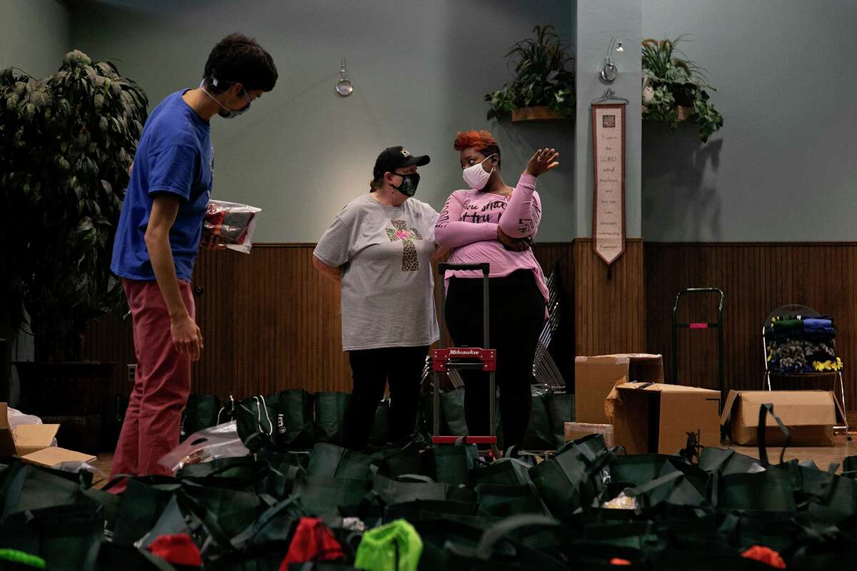 Bolunteer Latresha Stallworth, right, chats with Communities Under the Bridge Executive Director Dianne Talbert on Dec. 23, 2020. Stallworth and other volunteers including Daniel Szabo, far left, were at the East Side nonprofit filling Christmas bags for clients.
