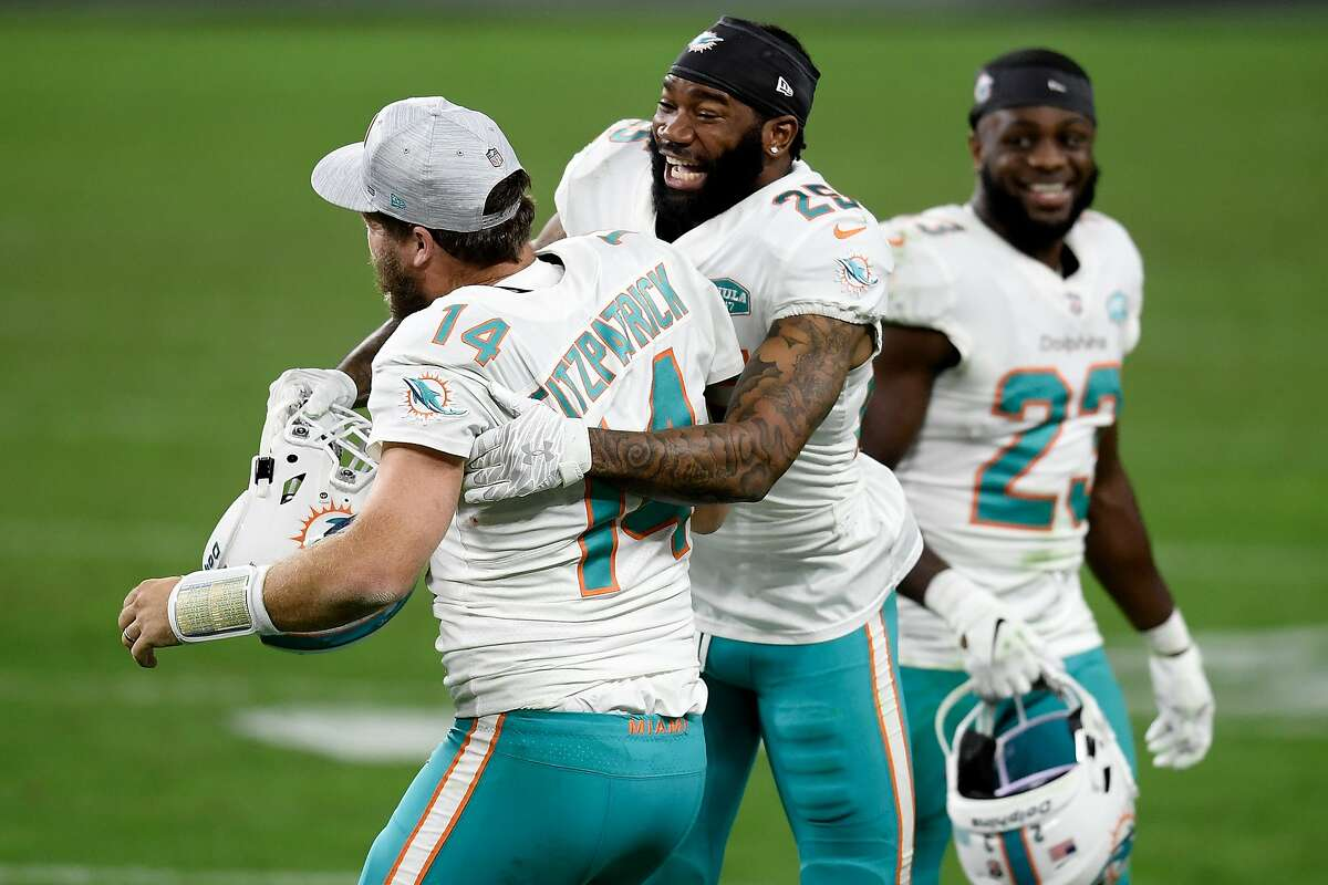 Xavien Howard (25) of the Dolphins celebrates with Ryan Fitzpatrick (14) after a last-second 44-yard field goal by Jason Sanders won the game for Miami.