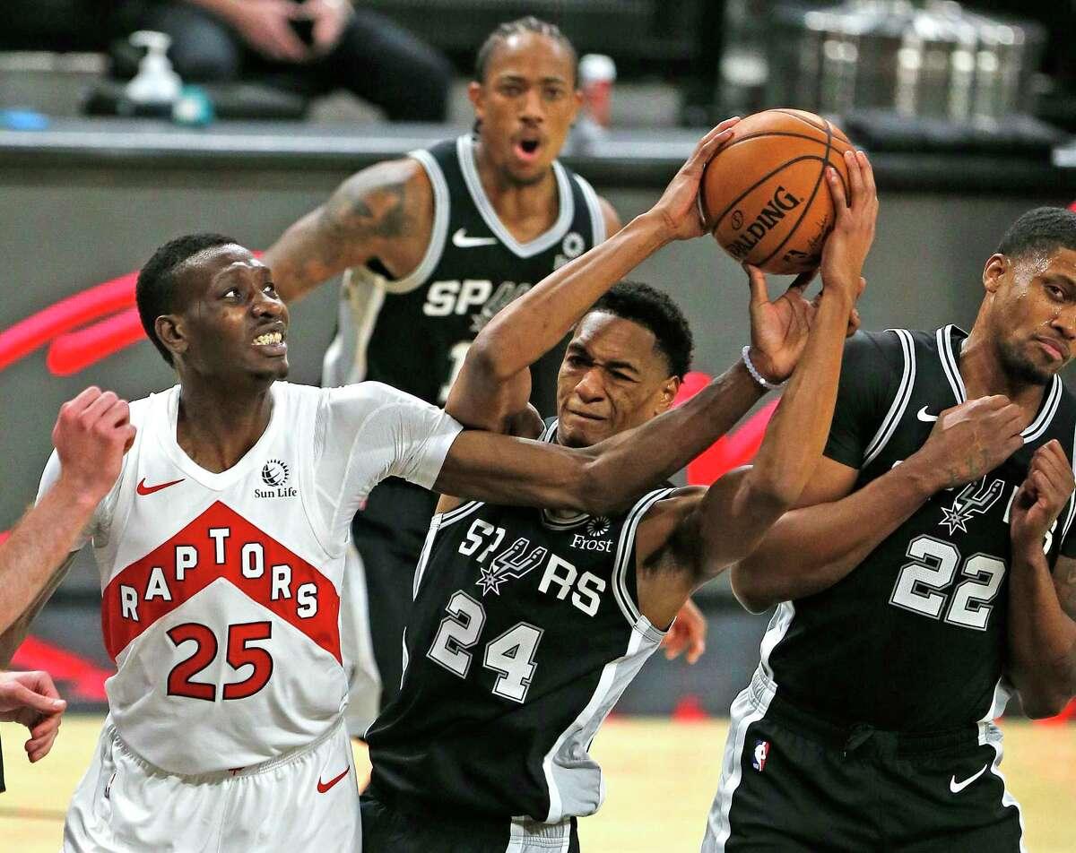 San Antonio Spurs guard Devin Vassell (24) grabs a rebound next to Chris Boucher #25 of the Toronto Raptors. Spurs v Raptors at AT&T Center on Saturday, Dec. 26, 2020.