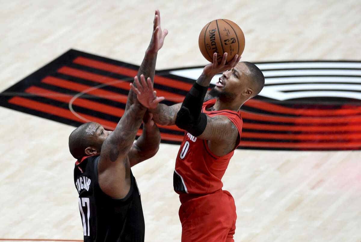 Portland Trail Blazers guard Damian Lillard drives to the basket on Houston Rockets forward P.J. Tucker, left, during the first half of an NBA basketball game in Portland, Ore., Saturday, Dec. 26, 2020. (AP Photo/Steve Dykes)