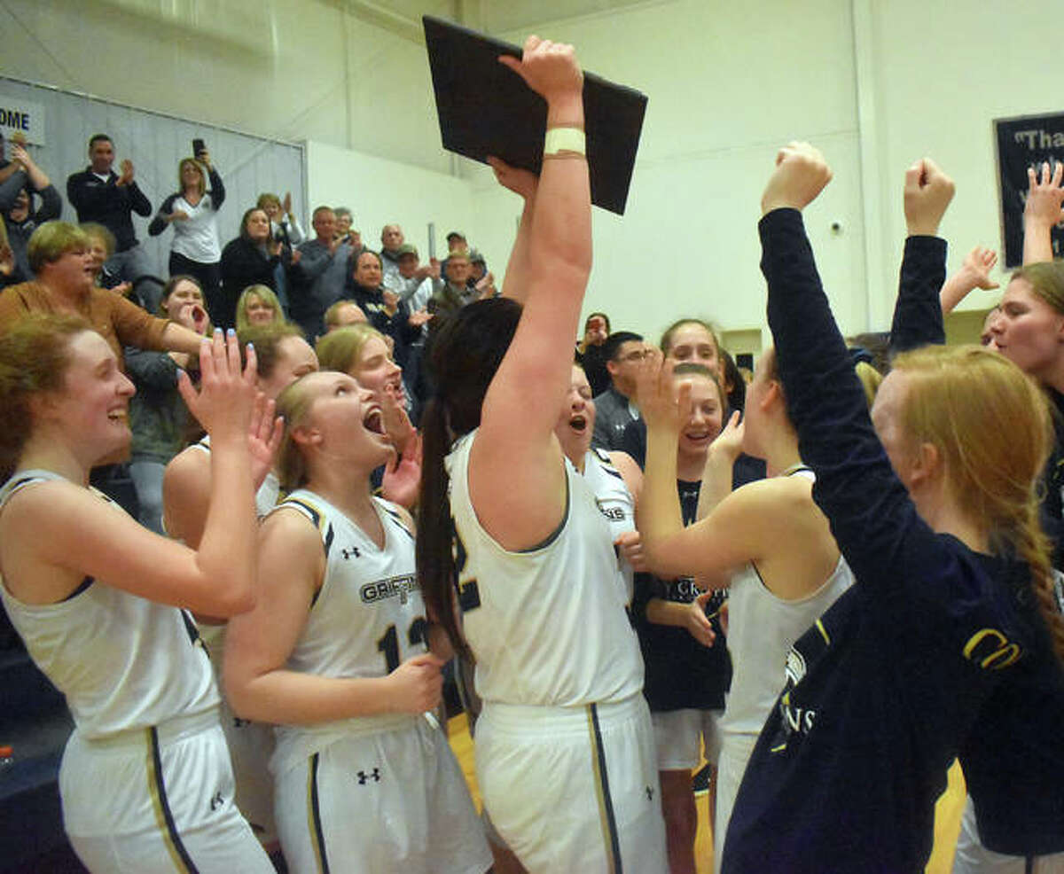 The Father McGivney Griffins celebrate with the Class 1A Christ Our Rock Lutheran Sectional championship plaque after defeating Jacksonville Routt Catholic on Thursday in Centralia.