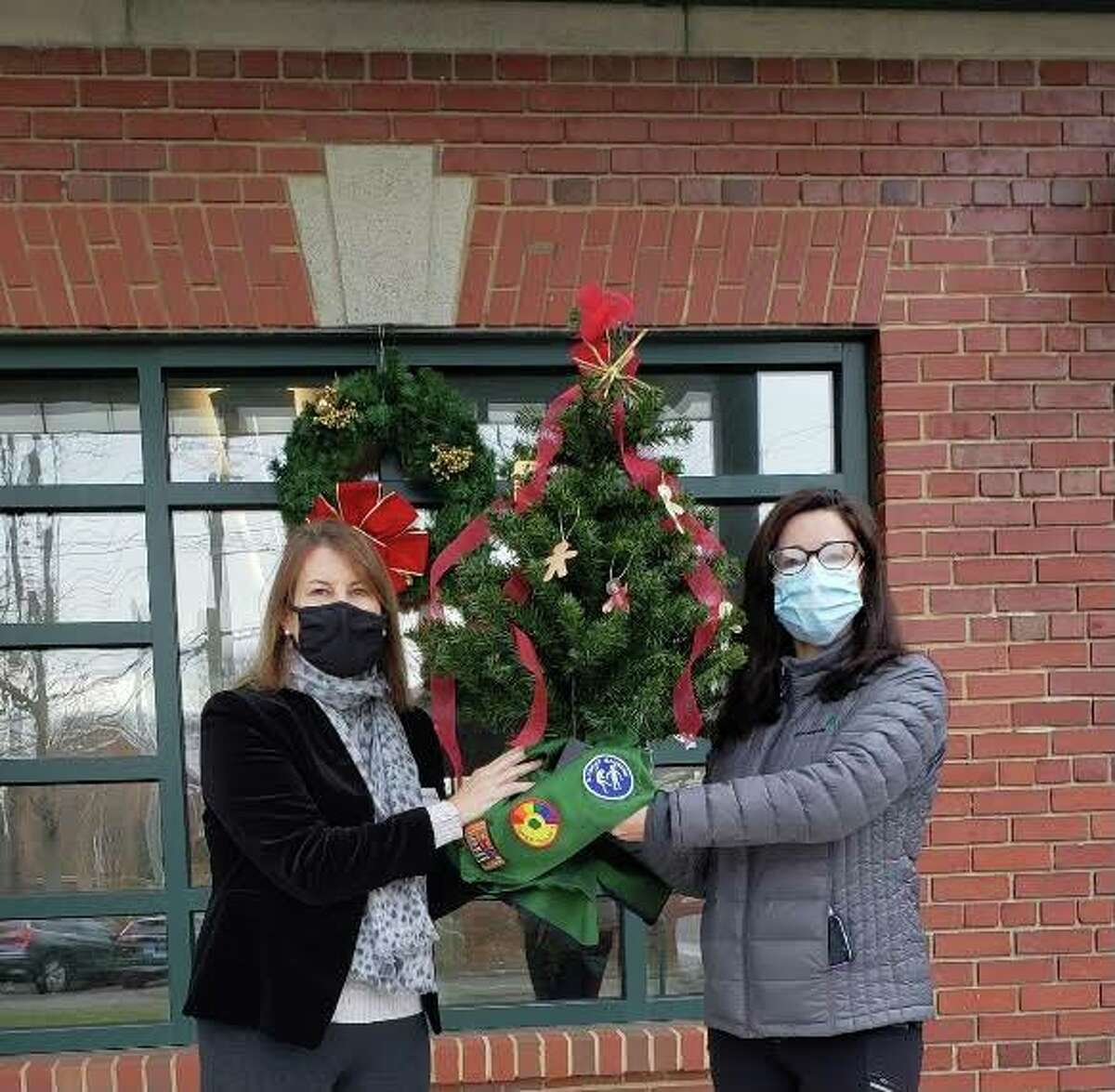 Anne Murdock, River House's development director, left, accepts a tree decorated by Greenwich Girl Scouts from Greenwich Girl Scouts co-Service Unit Manager Kim Sushon, right.