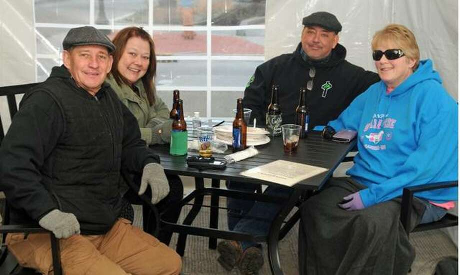 Joe Eagan of Florissant, Missouri, left, joins friends in the outdoor dining tent at Morrison's Irish Pub on Saturday. As temperatures drop, diners are finding it more challenging to follow Illinois' pandemic rules.