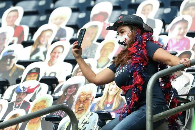 Houston Texans fan Debbie Chapa Brannon takes a photo with cardboard fan cutouts before an NFL football game against the Cincinnati Bengals at NRG Stadium on Sunday, Dec. 27, 2020, in Houston. Photo: Brett Coomer, Staff Photographer / © 2020 Houston Chronicle