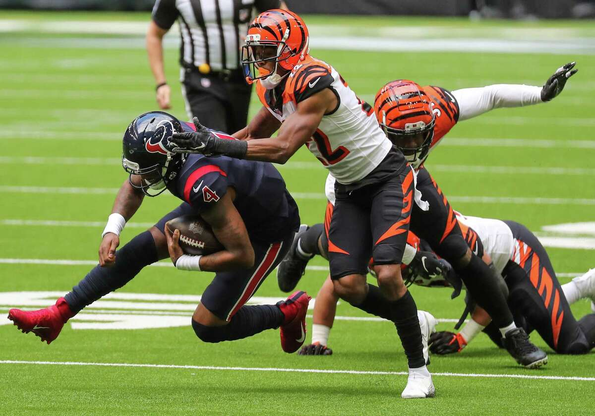 Houston Texans quarterback Deshaun Watson (4) is brought down by Cincinnati Bengals cornerback William Jackson (22) during the second quarter of an NFL football game at NRG Stadium on Sunday, Dec. 27, 2020, in Houston.