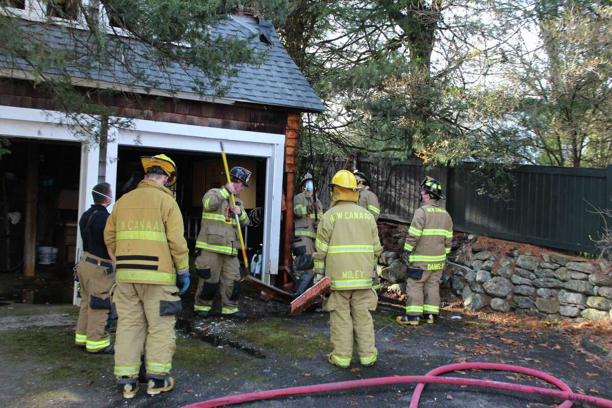 New Canaan firefighters clean up debris after fire struck a detached garage on Main Street Sunday afternoon, Dec. 27.