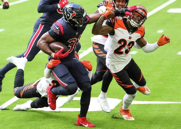 Houston Texans running back David Johnson (31) fights for extra yardage as he battles with Cincinnati Bengals cornerback Darius Phillips (23) on a run that went for a first down during the third quarter of an NFL football game at NRG Stadium on Sunday, Dec. 27, 2020, in Houston. Photo: Brett Coomer, Staff Photographer / © 2020 Houston Chronicle