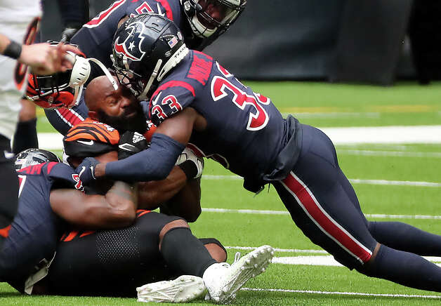 Houston Texans safety A.J. Moore (33) knocks off Cincinnati Bengals running back Samaje Perine's  helmet on a run up the middle during the fourth quarter of an NFL football game at NRG Stadium on Sunday, Dec. 27, 2020, in Houston. Photo: Brett Coomer, Staff Photographer / © 2020 Houston Chronicle