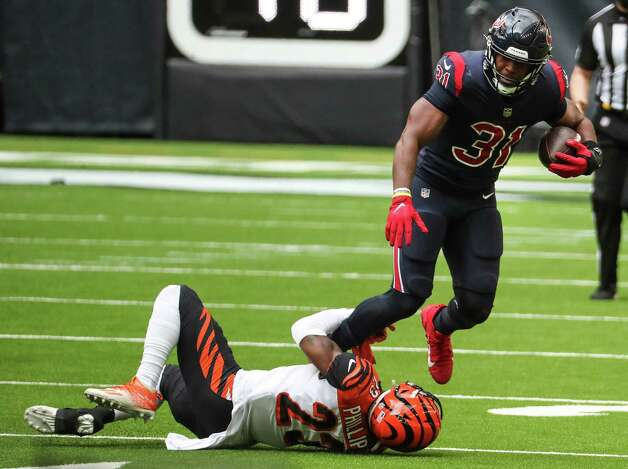 Houston Texans running back David Johnson (31) is tripped up by Cincinnati Bengals cornerback Darius Phillips (23) during the fourth quarter of an NFL football game at NRG Stadium on Sunday, Dec. 27, 2020, in Houston. Photo: Brett Coomer, Staff Photographer / © 2020 Houston Chronicle